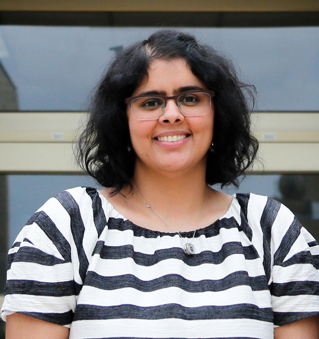 Mrinalini Hoon smiling into the camera wearing a striped shirt.